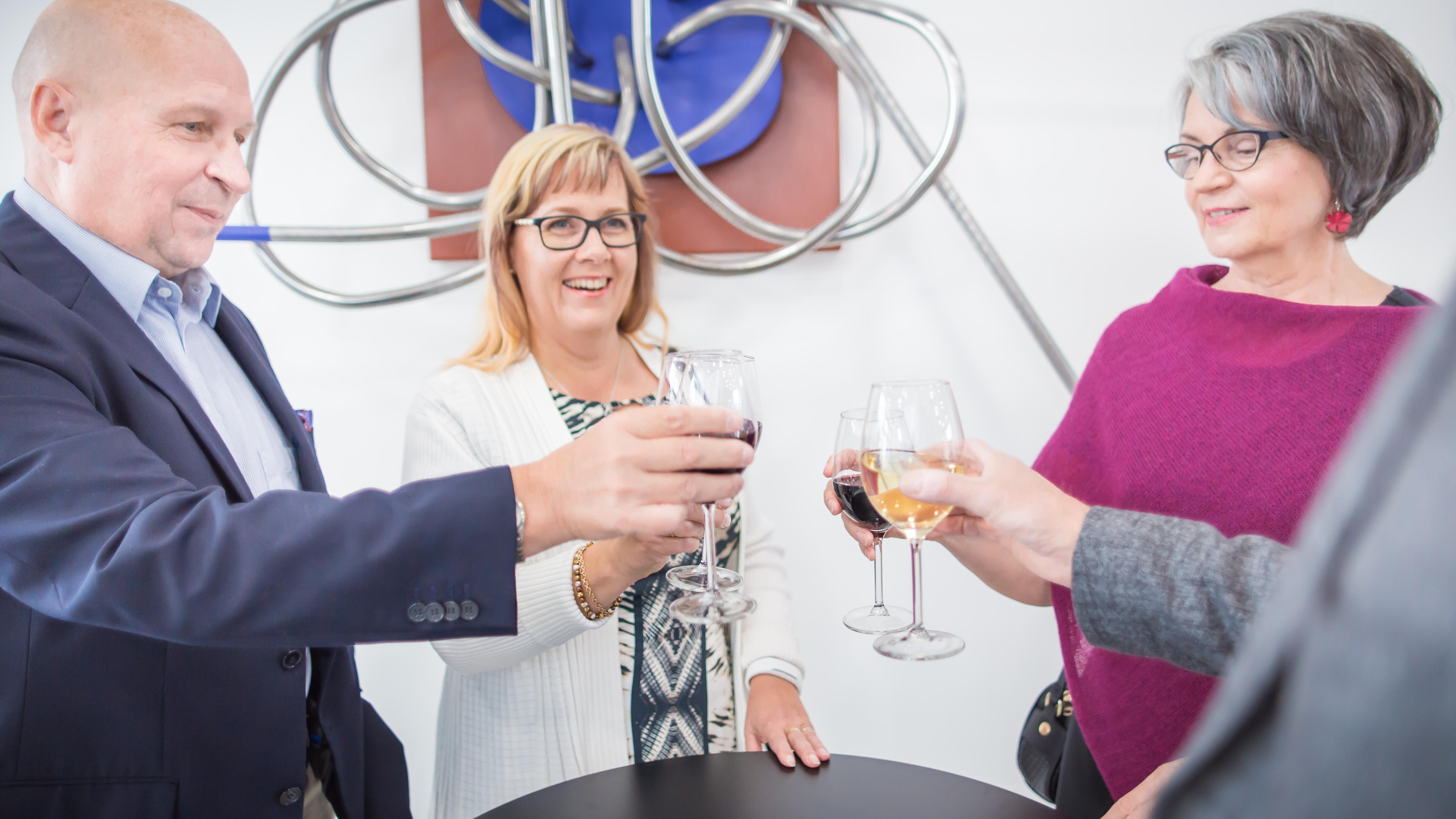 Seurue nauttii viinilasilliset Kangasala-talon aulassa.